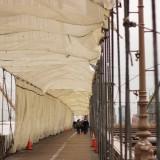 в некоторых частях, впрочем, он еще не до конца покрашен, покрытие обновляют и, защищающие пешеходов, полотна красиво полощутся на ветру